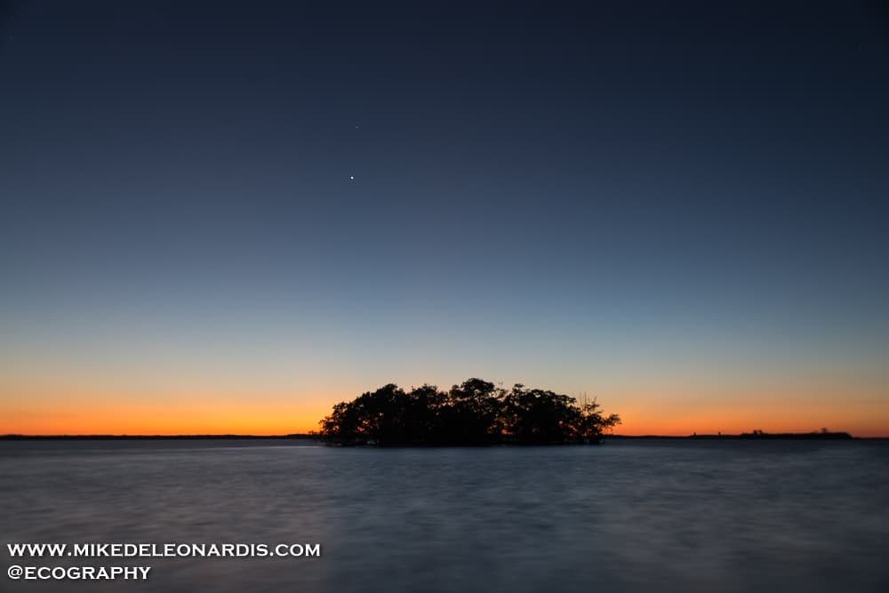 I shot a 4 hour sunset time-lapse video because on this winter day in South Florida the sky was cloudless. As the sun got below the horizon I noticed a unique color spectrum that is rarely seen in South Florida because of the clouds. Aside from the colors, Venus and Mars were setting right behind the sun. I used a long exposure to bring out the brightness of Venus and to also blur the waves approaching me.